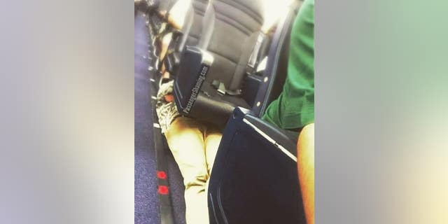 A passenger was seen laying down on an airplane floor, tucked underneath several seats on an unknown airline.