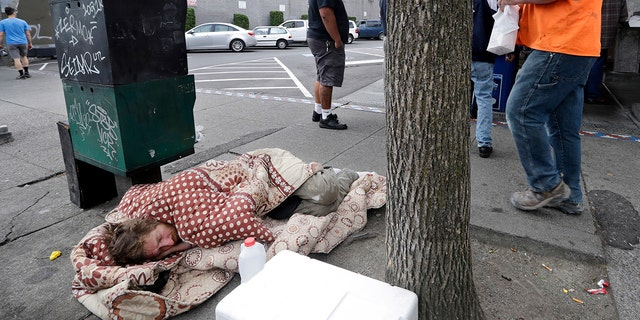 FILE - In this May 24, 2018 file photo, a man sleeps on the sidewalk as people behind line up to buy lunch at a Dick's Drive-In restaurant in Seattle. (AP Photo/Elaine Thompson, File)