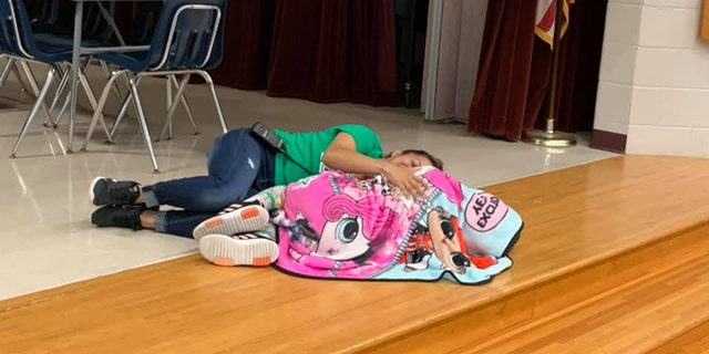Ms. Esther climbed up on stage and laid next to a student who was struggling with the noisy cafeteria.