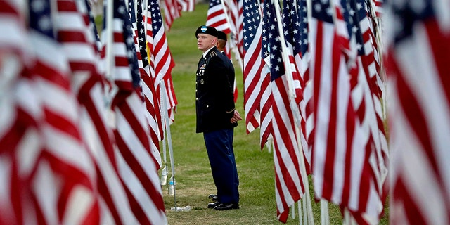 U.S. Army personnel stand amongst nearly 3,000 flags at sunrise on Sept. 11 in Tempe, Ariz. as they listen to the reading of the names of those killed on September 11, 2001. The flags are part of the annual Tempe Healing Field 9/11 memorial.(AP)