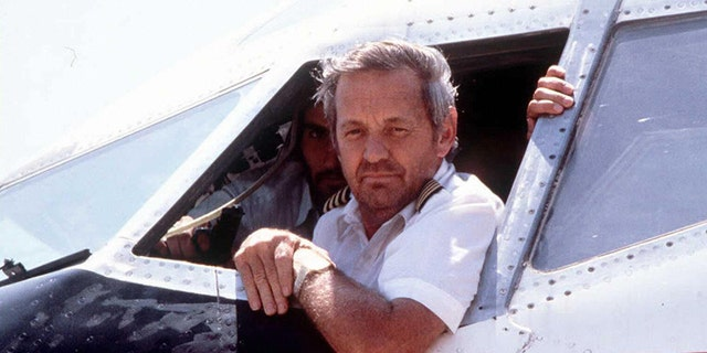 This file photo taken 19 June 1985 at the Beirut airport, in Lebanon, shows former TWA pilot John Testrake (R) answering journalists' questions with a gun pointed near his head during a tense 17-day standoff when hijackers diverted a Trans World Airlines Boeing jet carrying 146 passengers and crew. (Photo credit should read NABIL ISMAIL/AFP/Getty Images)