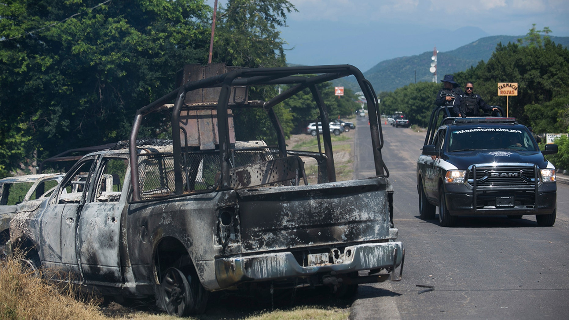 These burned out police vehicles contained the bodies of dead officers. (AP)