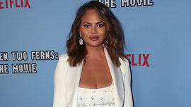 Chrissy Teigen poses topless after getting breast implants removed