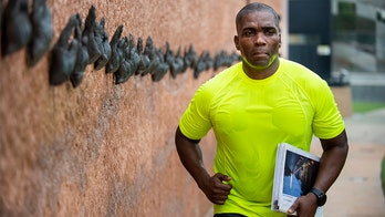 Army Reserve officer runs while carrying binder with names of US service members who died in Vietnam