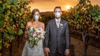 Couple poses for wildfire wedding photo during smoky ceremony at California winery