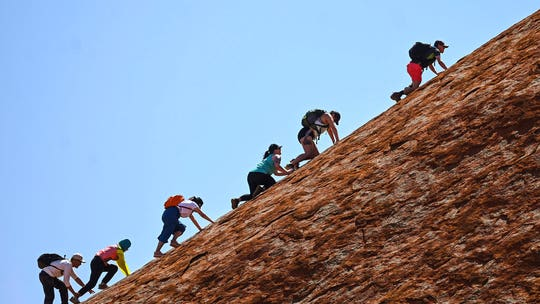 Australia's Uluru scaled by final climbers before ban on sacred site goes into effect
