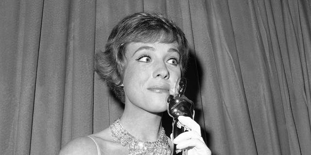 "This April 6, 1965 file photo shows actress Julie Andrews holding her best actress Oscar for ""Mary Poppins"" in Santa Monica, Calif. (AP Photo, File)"