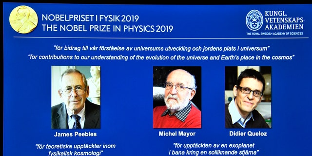 A screen displays the portraits of the laureates of the 2019 Nobel Prize in Physics, with left to right, James Peebles, Michel Mayor and Didier Queloz, during a news conference at the Royal Swedish Academy of Sciences in Stockholm, Sweden, on Tuesday Oct. 8, 2019. (Claudio Bresciani / TT via AP)