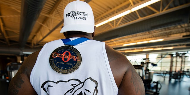 Tech. Sgt. Cook displays his medal from the United States Powerlifting Association's annual Olympia Pro Powerlifting Competition where he raw bench pressed 551 pounds. (U.S. Air Force photo by Senior Airman Jonathon Carnell)