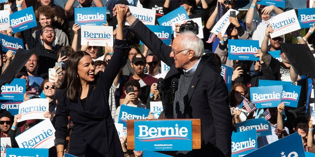 Democratic presidential candidate Sen. Bernie Sanders, I-Vt., right, is introduced by Rep. Alexandria Ocasio-Cortez, D-N.Y., during a campaign rally, Saturday, Oct. 19, 2019, in the Queens borough of New York. (AP Photo/Mary Altaffer)