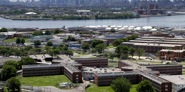 The Rikers Island jail complex, set against the backdrop of the New York City skyline.