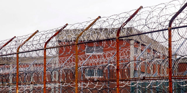 In this March 16, 2011, file photo, a security fence surrounds inmate housing on the Rikers Island correctional facility in New York. (AP Photo/Bebeto Matthews)