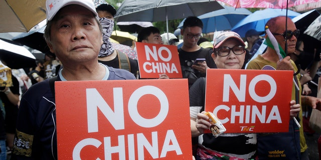 """Hong Kong students and Taiwanese supporters hold slogans during a march in Taipei, Taiwan, Sunday, Sept. 29, 2019. Sunday's demonstration was part of global """"anti-totalitarianism"""" rallies planned in over 60 cities worldwide, including in Australia and Taiwan, to denounce """"Chinese tyranny."""" (AP Photo/Chiang Ying-ying)"""