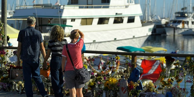 In this Sept. 6 photo, people visit a growing memorial to the victims who died aboard a dive boat that caught fire. (AP Photo/Mark J. Terrill,File)