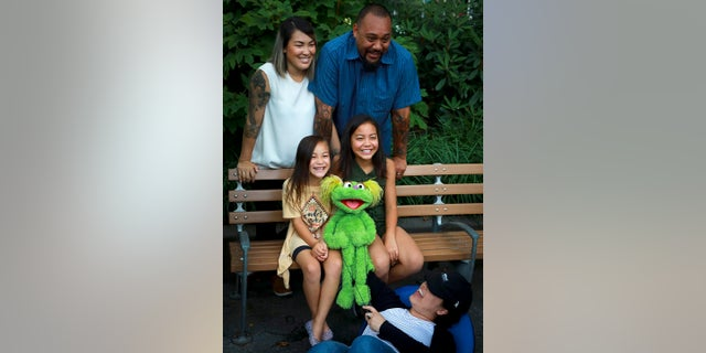 "Jaana (top left) and Sam Woodbury, from Irvine, Cali., and their daughters Salia, 10 (seated right), and Kya, 6, with ""Sesame Street"" Muppet Karli and puppeteer Haley Jenkins in New York. (AP Photo/Bebeto Matthews)"