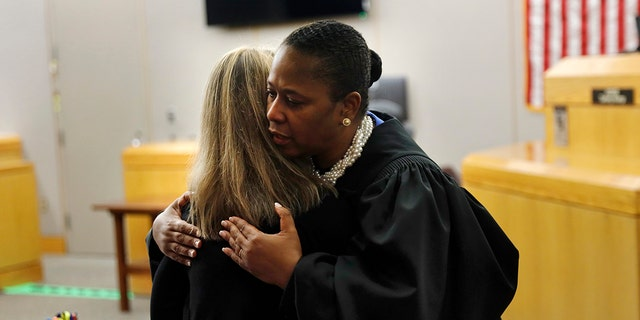 State District Judge Tami Kemp gives a hug to former Dallas police officer Amber Geiger before Geiger leaves for prison on Wednesday, October 2, 2019 in Dallas. Geiger, who said she misled a neighbor's apartment in Botham Jean for her own and fatally shot him in her living room, was sentenced to a decade in prison. (Tom Fox / The Morning News in Dallas via AP, Pool)
