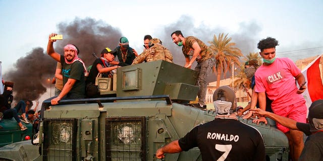 Anti-government protesters confront a soldier from the Federal Police Rapid Response Forces before they burn the armored vehicle, during a demonstration in Baghdad, Iraq, Thursday, Oct. 3, 2019.