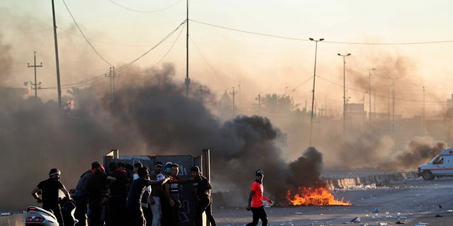 "Anti-government protesters set fires and close a street during a demonstration in central Baghdad on Friday. Security forces opened fire, killing some protesters and injuring dozens, hours after Iraq's top Shiite cleric warned both sides to end four days of violence ""before it's too late."" (AP Photo/Khalid Mohammed)"