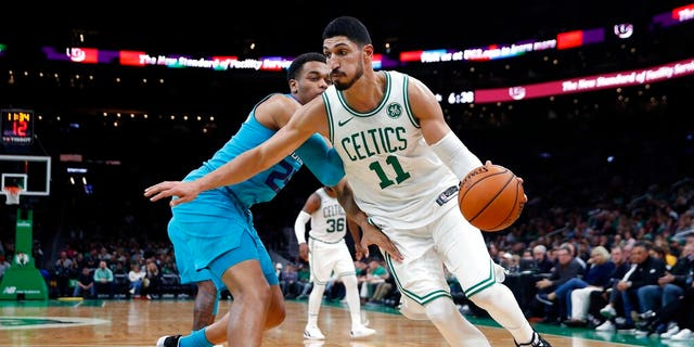 Boston Celtics' Enes Kanter (11) drives past Charlotte Hornets' PJ Washington (25) during the first half of a preseason NBA basketball game in Boston.