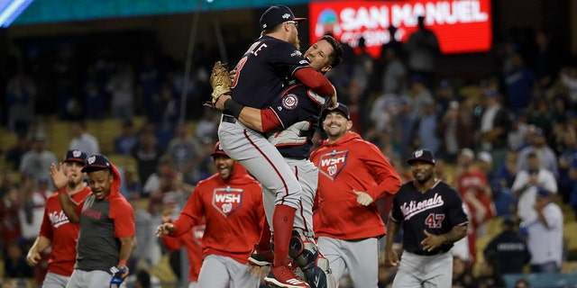 Washington Nationals pitcher Sean Doolittle, left, and catcher Yan Gomes leap in celebration after the team's 7-3 win in Game 5 of a baseball National League Division Series against the Los Angeles Dodgers on Wednesday, Oct. 9, 2019, in Los Angeles. (Associated Press)