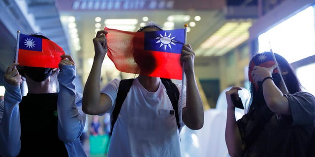 People hold Taiwanese flags as they join others at a rally to mark Taiwan's National Day, in the Tsim Sha Tsui district in Hong Kong, Thursday, Oct. 10, 2019.