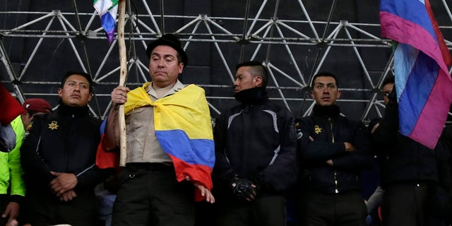 A policeman detained by anti-government protesters is made to hold an indigenous banner while standing on a stage in Quito, Ecuador, on Thursday. (AP Photo/Dolores Ochoa)