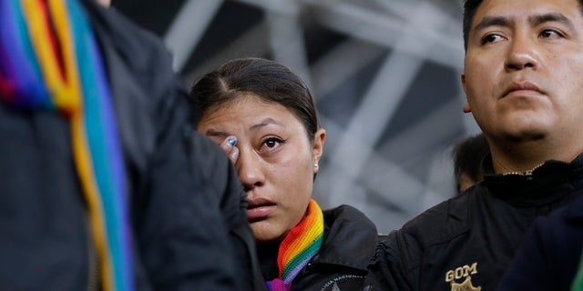 A policewoman, who was detained by anti-government protesters, cries while standing on a stage at the Casa de Cultura in Quito. (AP Photo/Fernando Vergara)