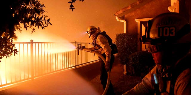 In this Thursday, Oct. 10, 2019 photo, Los Angeles City firefighters battle the Saddleridge fire near homes in Sylmar, Calif. (Associated Press)