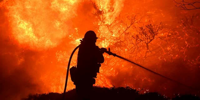 The Saddleridge glow flares adult nearby a firefighter in Sylmar, Calif., Thursday, Oct. 10, 2019. (Associated Press)