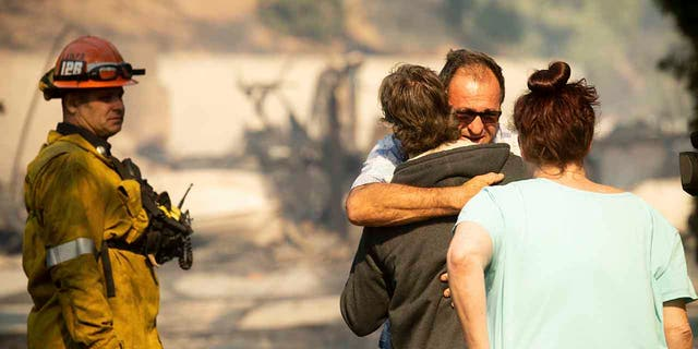 Eyed Jarjour amenities a neighbor who mislaid his Jolette Ave. home to a Saddleridge Fire on Friday, Oct. 11, 2019, in Granada Hills, Calif. (Associated Press)