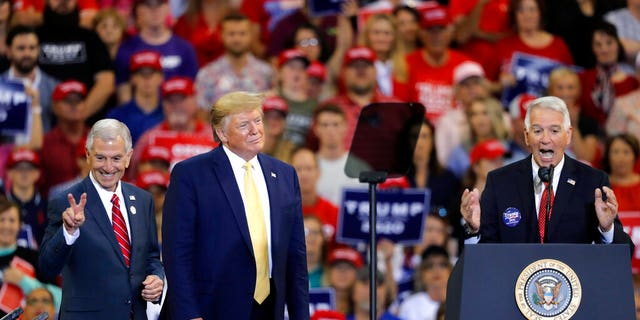 President Donald Trump introduces Louisiana Republican gubernatorial candidates Eddie Rispone, left, and Ralph Abraham, during his campaign rally on the eve of the Louisiana election, in Lake Charles, La., Friday, Oct. 11, 2019. The two are running against incumbent Democrat Gov. John Bel Edwards.
