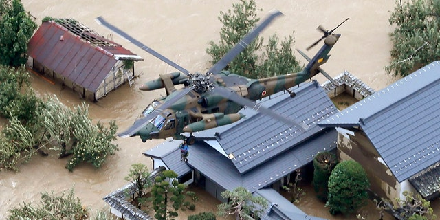 A resident is rescued by a Japan Self-Defense Force helicopter as the house is submerged in muddy waters after an embankment of the Chikuma River broke because of Typhoon Hagibis, in Nagano, central Japan, Sunday, Oct. 13, 2019. Rescue efforts for people stranded in flooded areas are in full force after a powerful typhoon dashed heavy rainfall and winds through a widespread area of Japan, including Tokyo.(Yohei Kanasashi/Kyodo News via AP)