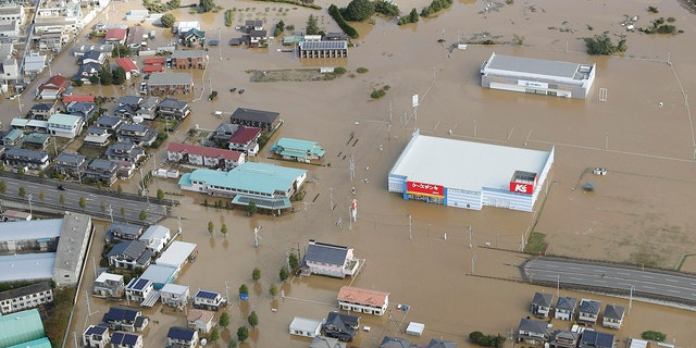 Houses are submerged in muddy waters in Sukagawa, Fukushima prefecture, Typhoon Hagibis hits the area, Northern Japan, Sunday, Oct. 13, 2019. Rescue efforts for people stranded in flooded areas are in full force after a powerful typhoon dashed heavy rainfall and winds across a widespread area of Japan, including Tokyo. (Takuya Inaba / Kyodo News via AP)