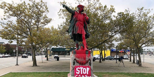 "A sign reading ""stop celebrating genocide"" sits at the base of a statue of Christopher Columbus on Monday in Providence, Rhode Island, after it was vandalized with red paint on the day named to honor him as one of the first Europeans to reach the New World. (AP Photo/Michelle R. Smith)"