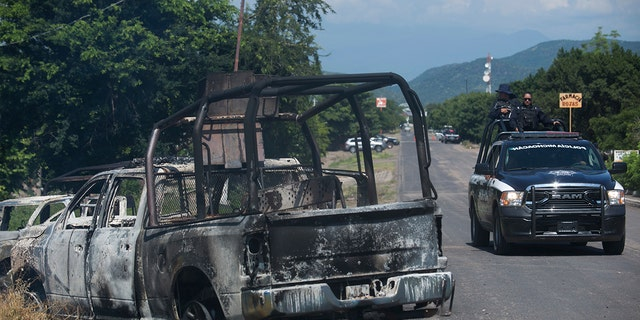 A charred truck that belongs to Michoacan state police sits on the side of the road after it was burned during an attack, as state police drive past in El Aguaje, Mexico, Monday, Oct. 14, 2019. At least 13 police officers were killed and three others injured Monday in the ambush.