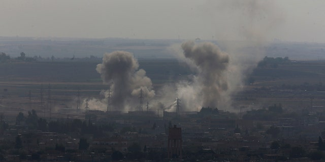 In this photo taken from the Turkish side of the border between Turkey and Syria, in Ceylanpinar, Sanliurfa province, southeastern Turkey, smoke billows from targets in Ras al-Ayn, Syria, caused by bombardment by Turkish forces, Tuesday, Oct. 15, 2019.