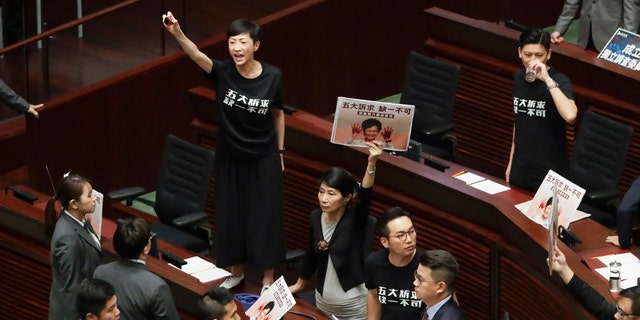 Pro-democracy lawmakers protest as Hong Kong Chief Executive Carrie Lam delivers a speech at chamber of the Legislative Council in Hong Kong Wednesday, Oct. 16, 2019. Chanting pro-democracy lawmakers have interrupted the start of a speech that Lam was giving laying out her policies.