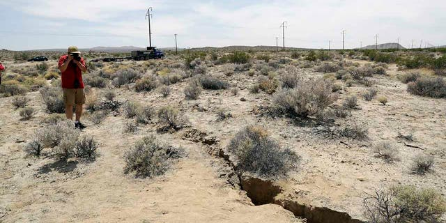 A visitor takes a photo of a crack in the ground following recent earthquakes near Ridgecrest, Calif., on July 7, 2019. (AP Photo/Marcio Jose Sanchez, File)