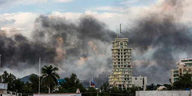 "Smoke from burning cars rises due in Culiacan, Mexico, Thursday, Oct. 17, 2019. An intense gunfight with heavy weapons and burning vehicles blocking roads raged in the capital of Mexico's Sinaloa state Thursday after security forces located one of Joaquín ""El Chapo"" Guzmán's sons who is wanted in the U.S. on drug trafficking charges."