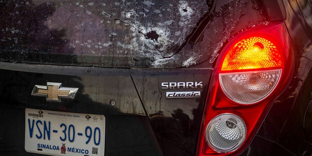 A car's rearview window is pierced with bullet holes amid a gunfight in Culiacan, Mexico, Thursday, Oct. 17, 2019. (AP Photo/Hector Parra)
