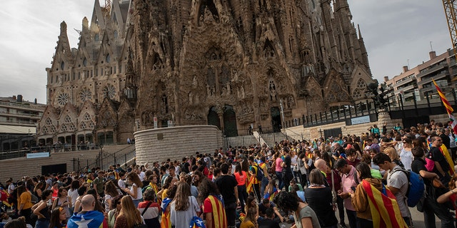 Demonstrators join a pro-independence gathering outside the Sagrada Família basilica during the fifth day of protests over the conviction of a dozen Catalan independence leaders in Barcelona, Spain, Friday, Oct. 18, 2019.