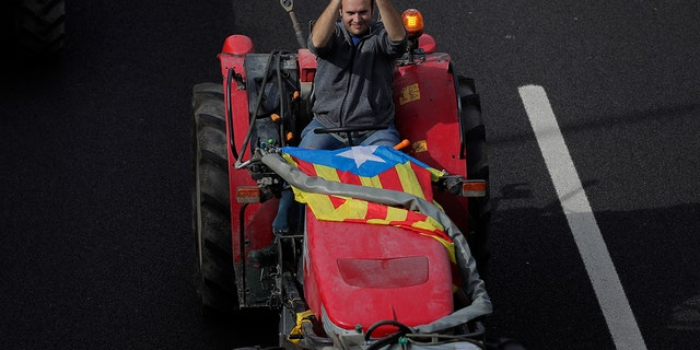 "A protester with an ""estelada"" or independence flag applauds as he drives a tractor entering the city on the fifth day of protests over the conviction of a dozen Catalan independence leaders in Barcelona, Spain, Friday, Oct. 18, 2019."