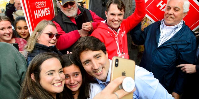 Liberal leader Justin Trudeau pose with supporters during a campaign stop in Orillia, Ontario on Friday Oct. 18, 2019.