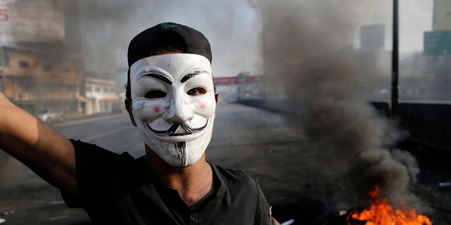 An anti-government protester blocks a highway that links to north Lebanon in east Beirut, Lebanon, Sunday, Oct. 20, 2019. Protests erupted in Lebanon after the government proposed new taxes criticized for hitting low income groups the hardest. (AP Photo/Hussein Malla)