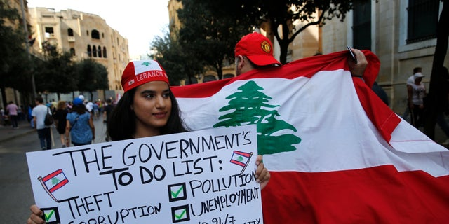Protesters hold banners during a demonstration in Beirut, Lebanon, Sunday, Oct. 20, 2019. Protests erupted in Lebanon over the last couple of days after the government proposed new taxes criticized for hitting low-income groups the hardest. (AP Photo/Hussein Malla)