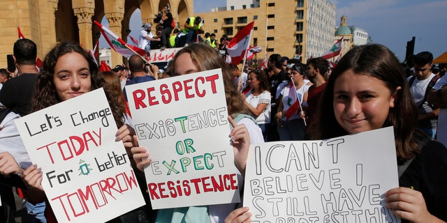 Anti-government protesters hold placards during a demonstration in Beirut, Lebanon, Sunday, Oct. 20, 2019. Protests erupted in Lebanon over the last couple of days after the government proposed new taxes criticized for hitting low-income groups the hardest. (AP Photo/Hussein Malla)