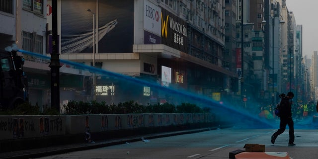 Police use blue dyed water to disperse protestors in Hong Kong, Sunday, Oct. 20, 2019. Hong Kong protesters again flooded streets on Sunday, ignoring a police ban on the rally and setting up barricades amid tear gas and firebombs. (AP Photo/Vincent Yu)