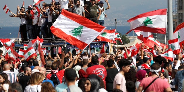 "Anti-government protesters chant slogans and wave their national flags at Martyr's Square, in downtown Beirut, Lebanon, Sunday, Oct. 20, 2019. Lebanon is bracing for what many expect to be the largest protests in the fourth day of anti-government demonstrations. Thousands of people of all ages were gathering in Beirut's central square Sunday waving Lebanese flags and chanting the, ""people want to bring down the regime."" (AP Photo/Hussein Malla)"