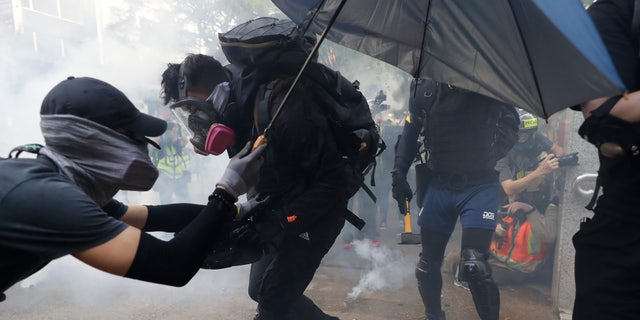 Protesters face police tear smoke in Hong Kong, Sunday, Oct. 20, 2019. Hong Kong protesters again flooded streets on Sunday, ignoring a police ban on the rally and setting up barricades amid tear gas and firebombs. (AP Photo//Mark Schiefelbein)