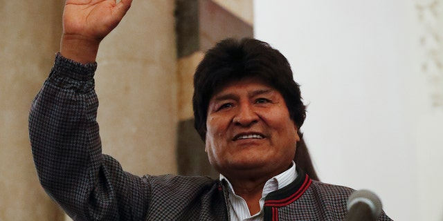 Bolivian President Evo Morales waves to supporters at the presidential palace in La Paz, Bolivia, after a first-round presidential election, Sunday, Oct. 20.